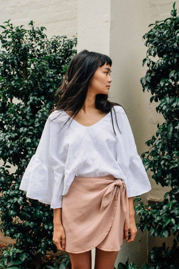 Model looks feminine in a rose wrap skirt against the willowy fabric of a white oversized tee