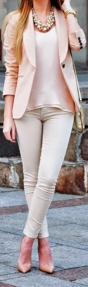 Model is wearing form-fitting beige pants, flowy top and fitted blazer in rose blush and nude stilettos