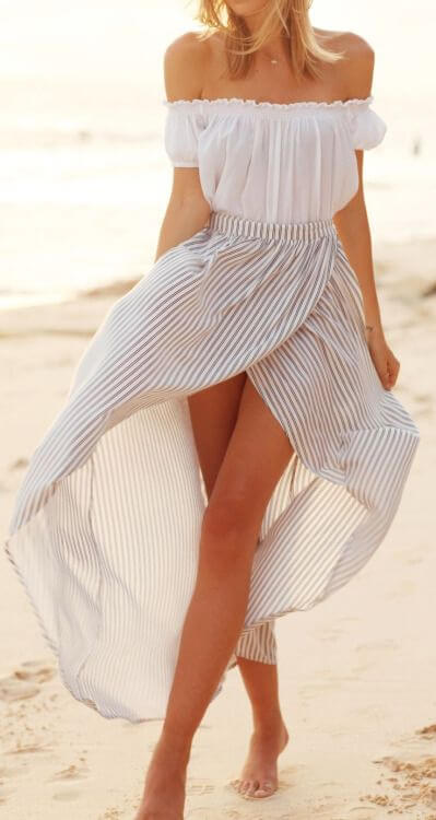 Model floats in a pairing of a white off-shoulder top and a white striped wrap skirt, barefoot with toes in the sand