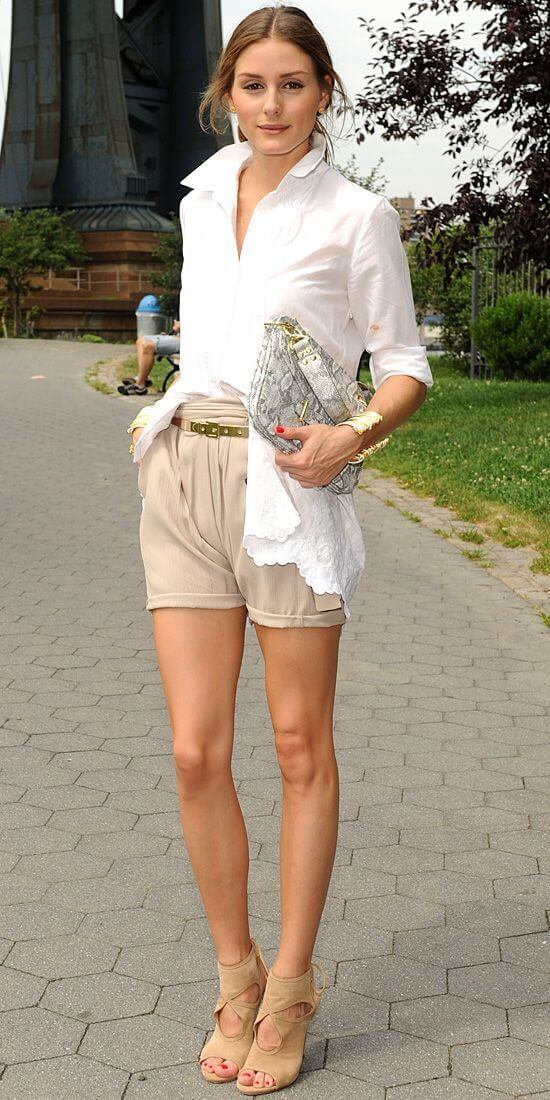 Model is seen in a white blouse paired with rolled-up beige shorts and matching open-toed sandals