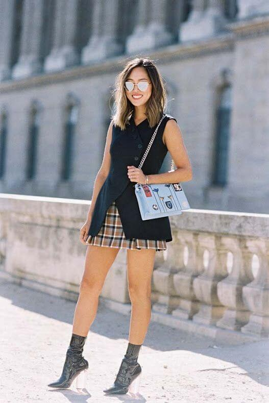 Model ravishes in a paid miniskirt against a basic black sleeveless double-breasted gilet, black patent leather boots accentuate the look