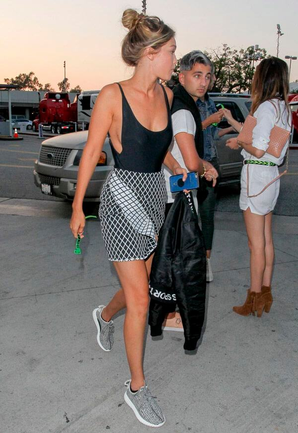 Model sports a dark gray and white patterned wrap skirt with a slink vest, topped off with Adidas sneakers