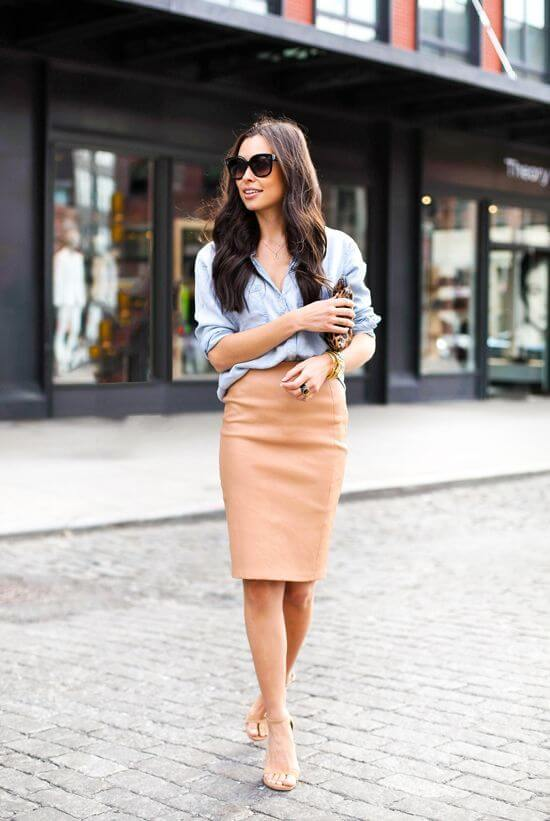 Model dons a denim button-down shirt and skirt, nude strappy sandals add an elegant feel