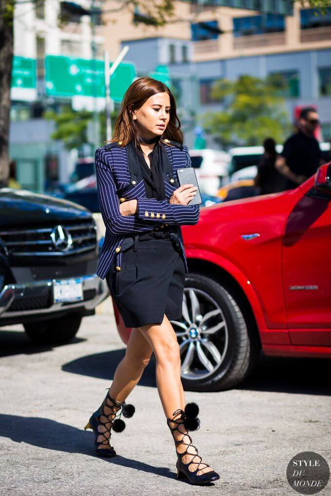 Model styles in a navy blue wrap skirt, loose blouse in the same color and a nautical fitted blazer, Gucci Heloise leather lace-up boots with mink detail for fun