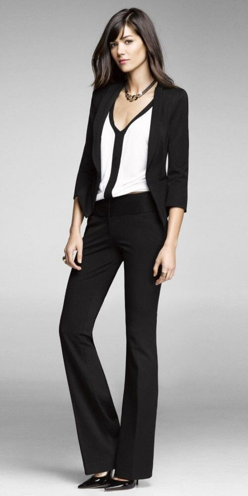 Model is wearing a loose-fitting blouse under a black jacket and black slacks, black heels to finish