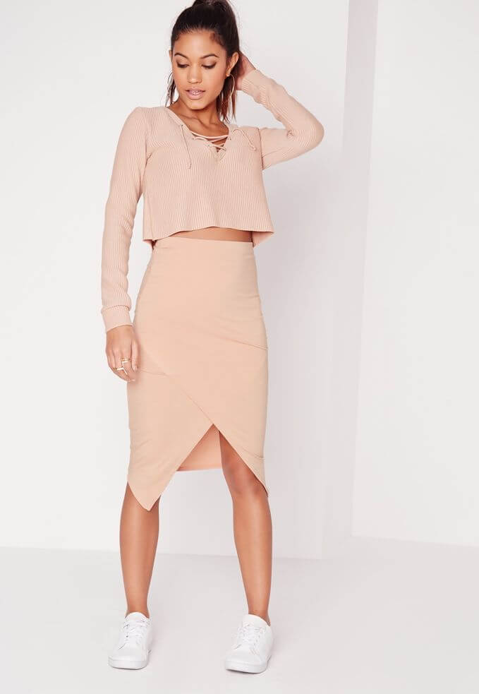 Model sports a sleek figure0hugging wrap skirt in pink and a loose top with a drawstring neckline, sporty trainers gives off a cool factor