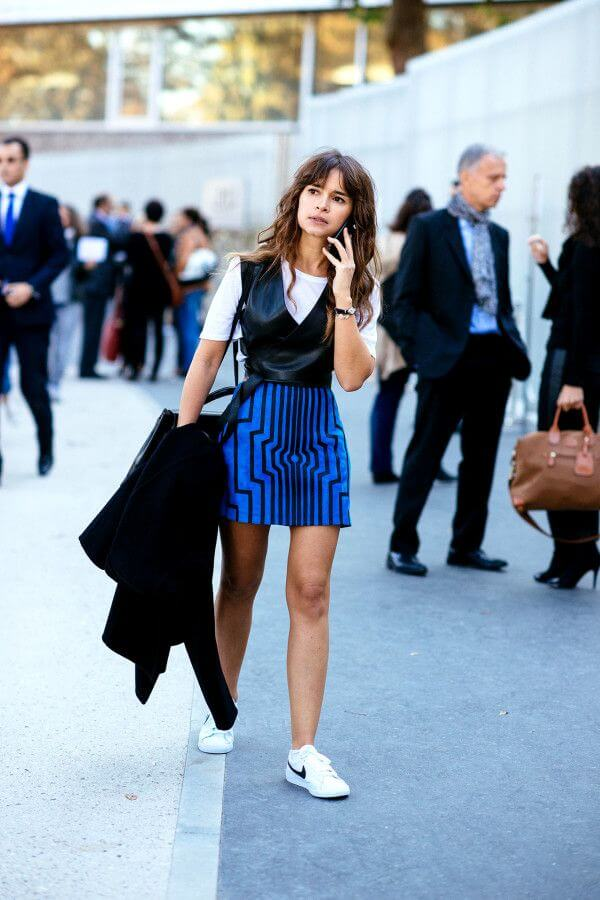 Model styles in a graphic blue cobalt skirt, white shirt and black leather waistcoat, Nike sneakers to accessorize