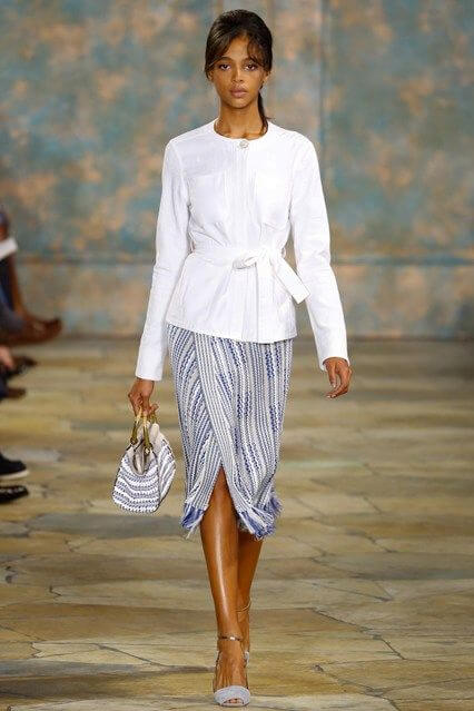 Model opts for a blue-and-white wrap midi skirt with a crisp longer-length white blouse tied at the waist