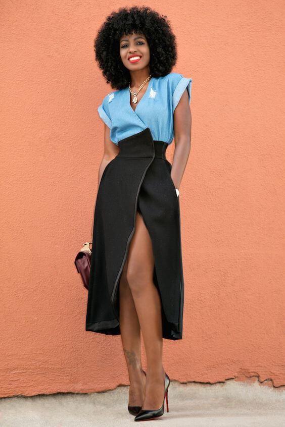 Model takes new proportions with a black midi wrap skirt paired with a denim blouse and pointy black stiletto heels
