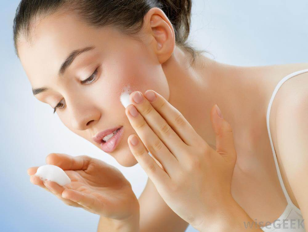 Woman applying skincare cream on her face