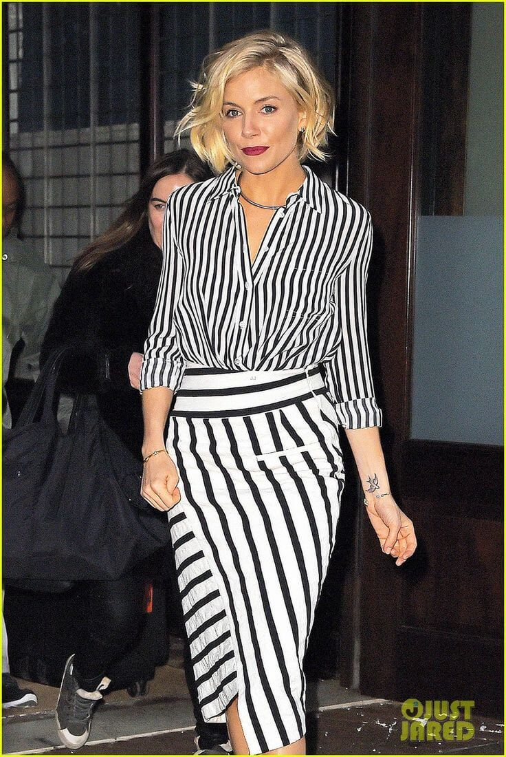 Embracing the trend by pairing asymmetrical black and white wrap skirt with a wrap blouse, heels to wrap up the outfit