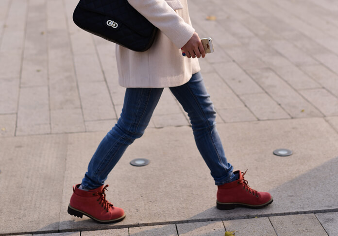 Woman in blue jeans going on the street with a phone in a hand