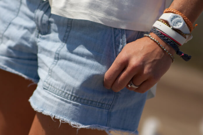 Woman in jean shorts, some nice accessories on the wrist