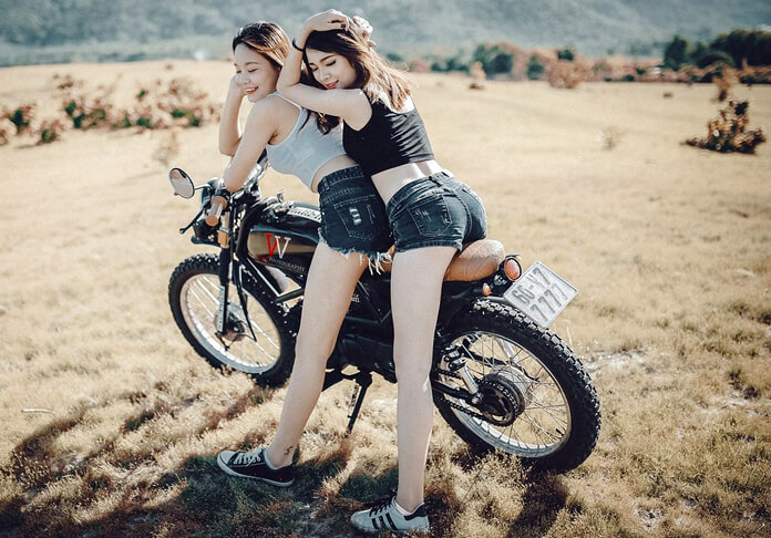 Pretty girls on a motorbike wearing denim shorts