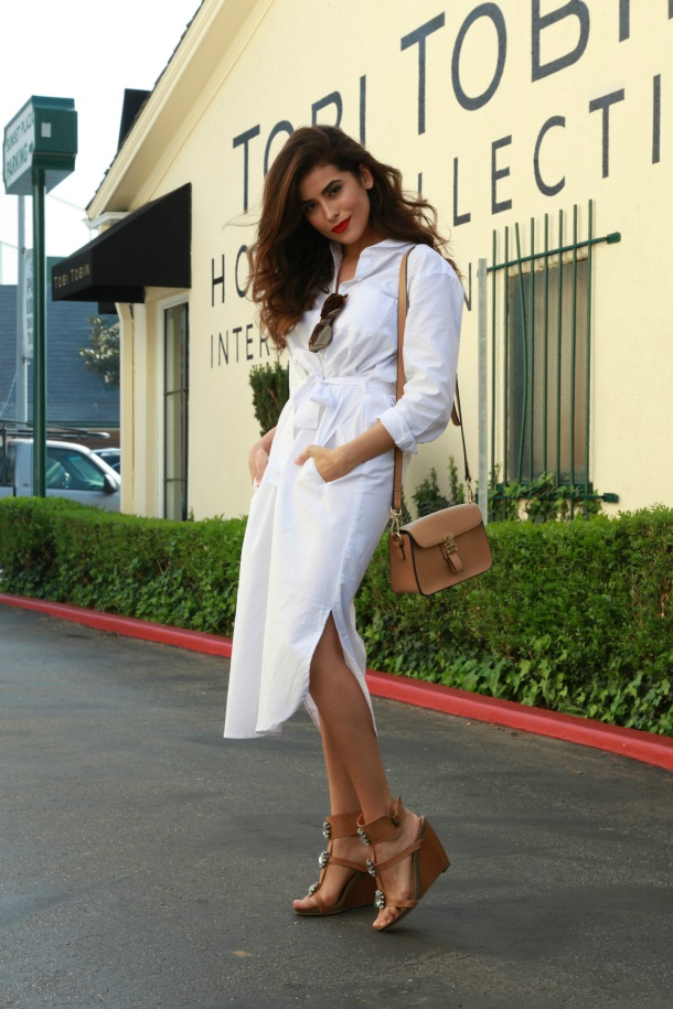 Beautiful woman in a white shirtdress with tie-up belt