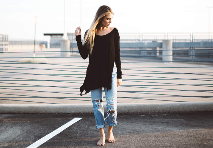 Pretty woman wearing torn jeans in a parking lot