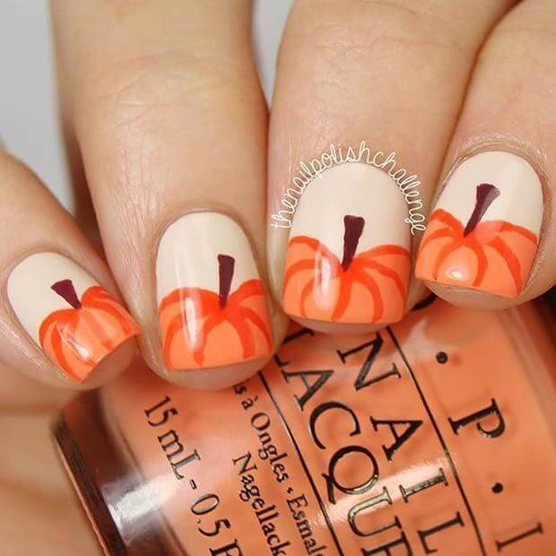 Beige nails with orange tips in the shape of pumpkins