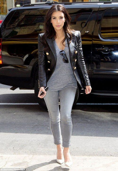 Kim Kardashian wearing gray skinny jeans with a draped gray T-shirt and black leather jacket