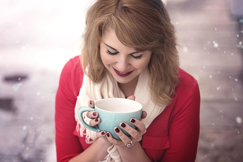 Woman holding tea cup with snowy background
