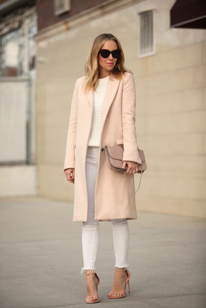 A blush-colored coat gives this white ensemble a refined touch.