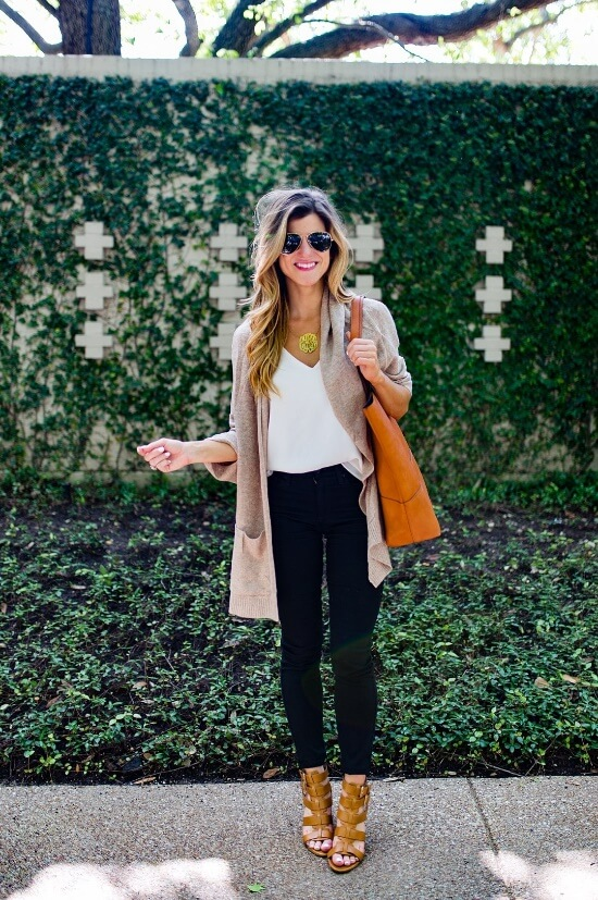 Woman in pair of skinny black jeans, a loose strappy top and longer draped pocket shrug cardigan