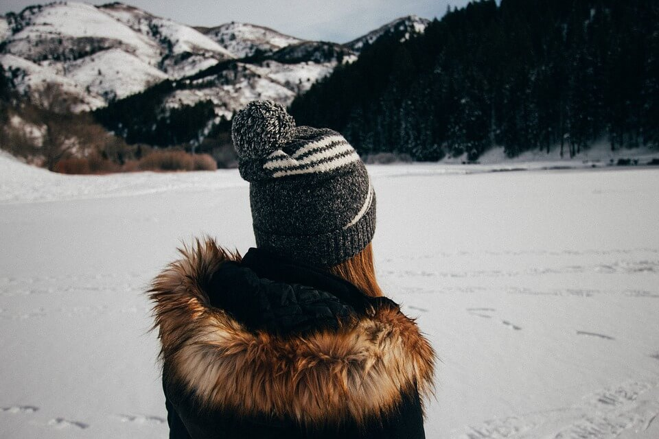woman looking out at snowy mountains wearing a beanie with a pom and a furry jacket