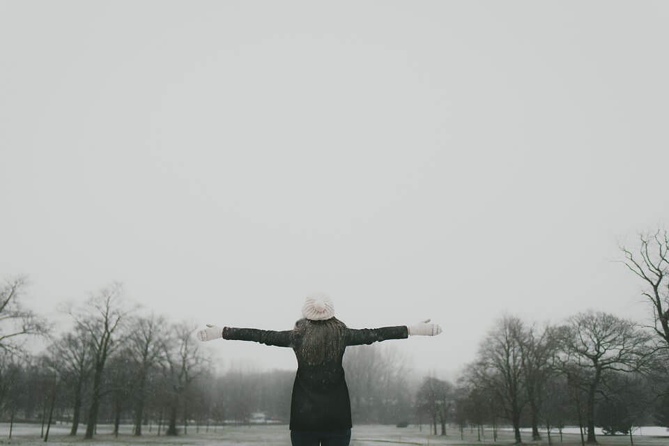 Woman standing with her arms outstretched in a park in the winter