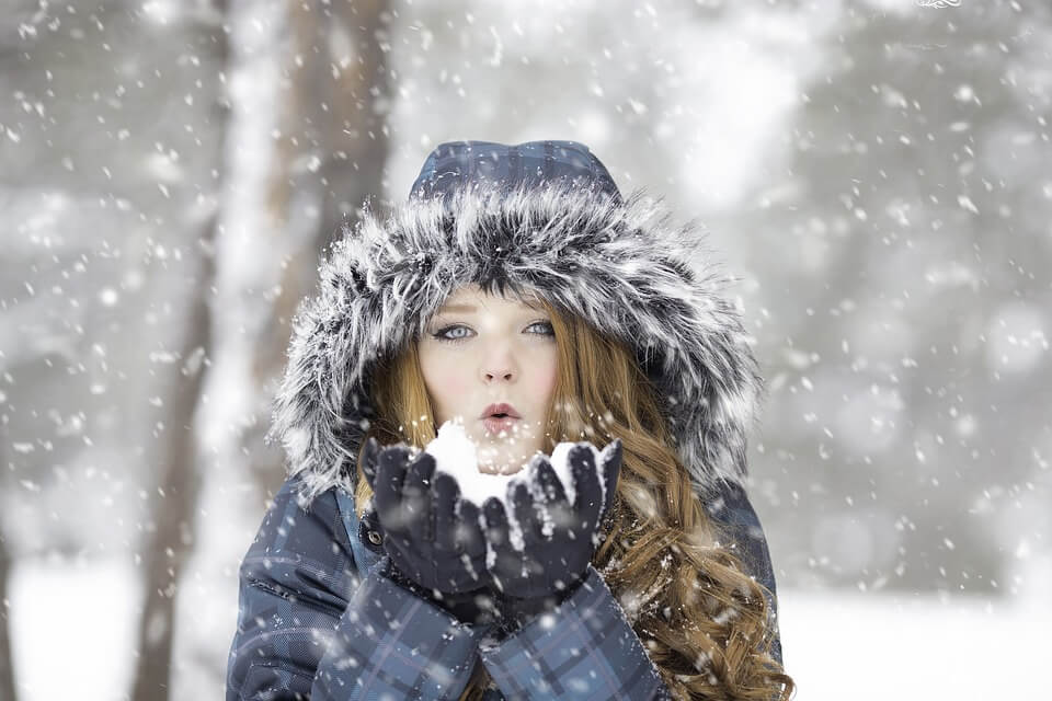 Woman wearing a big puffy jacket with a furry hood holding a piece of snow in her hands