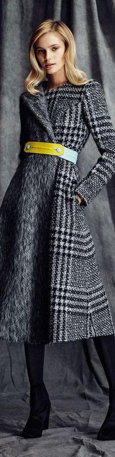A model is wearing a grey tweed coat with furry details and a bright colored belt