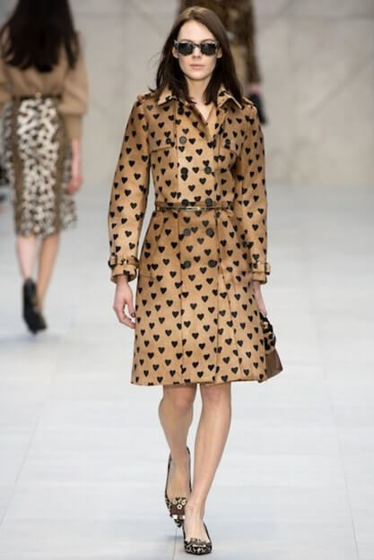 A model is wearing a deep beige trench coat with a pattern of black hearts all over it