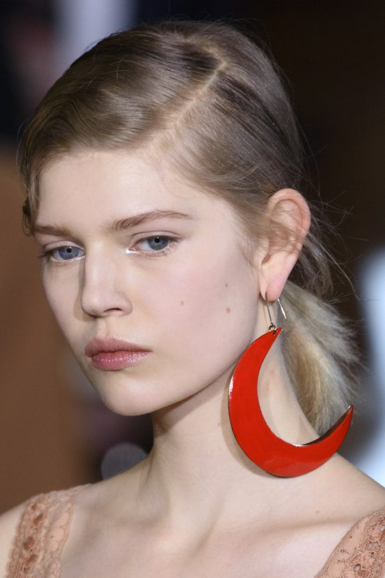 A model is wearing a very big plastic red earring