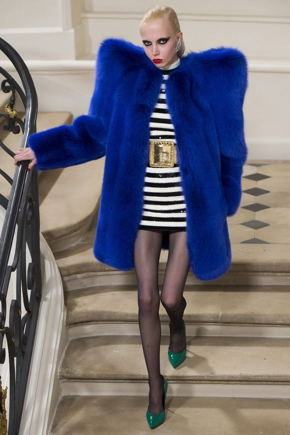 A model from YSL wears an oversize blue fur coat with extra wide shoulders, a black and white striped dress with a golden belt, and green pointy-toe heels