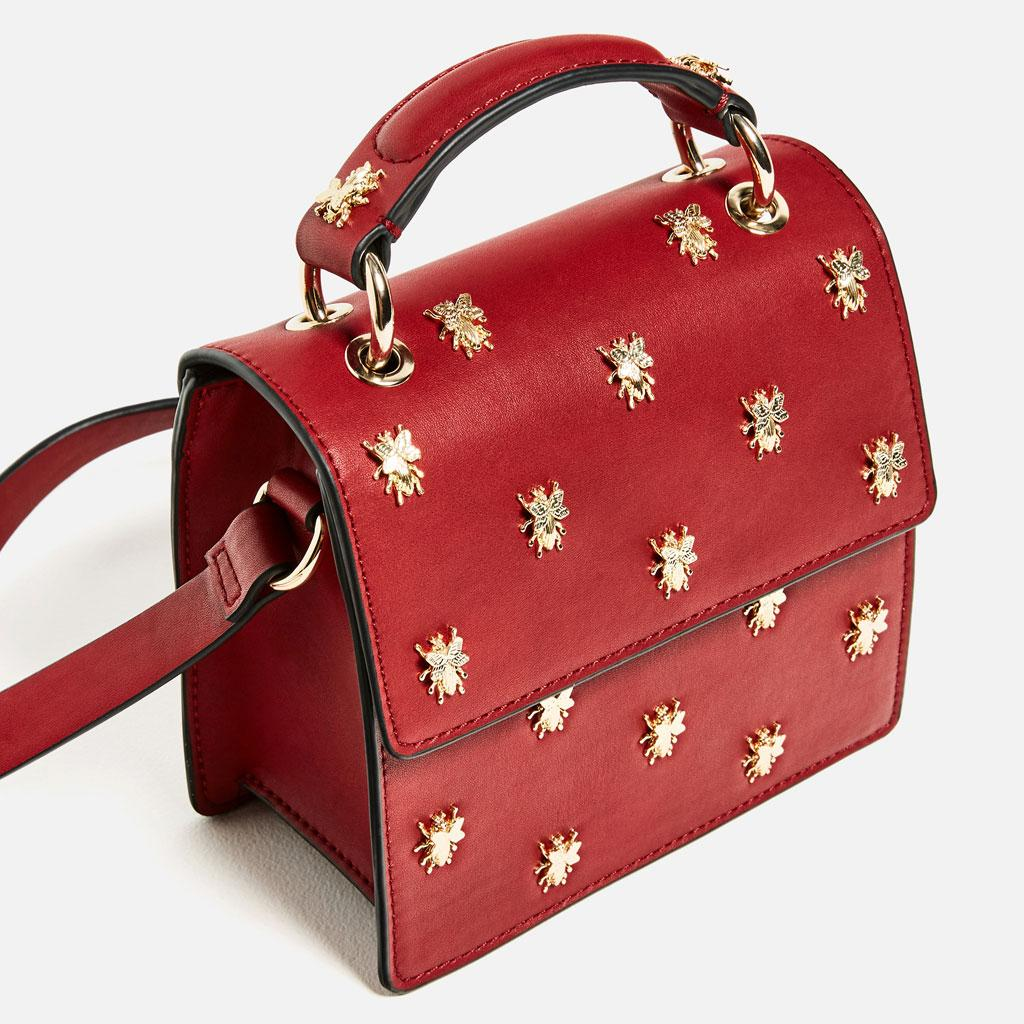 A small crossbody bag in red with golden bees on it