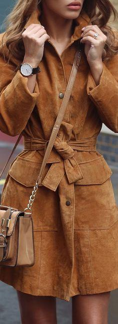 A woman is wearing a camel trench coat in suede, with a beige crossbody bag