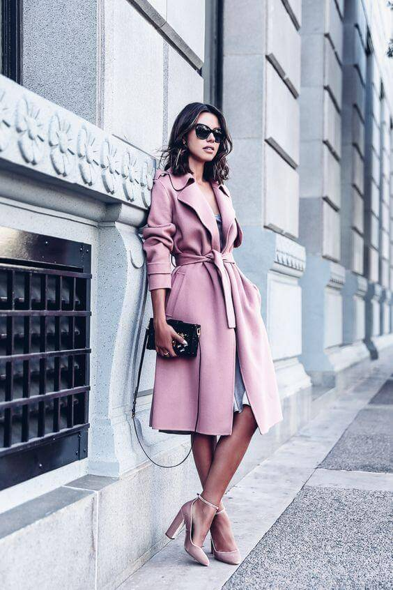 A woman is wearing a blush pink knee-length trench coat, with matching wide heel sandals, and a small black crossbody purse