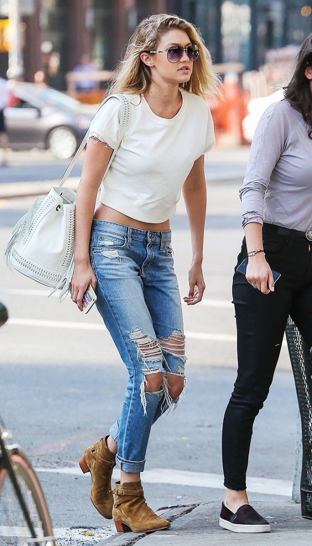 Gigi Hadid is wearing a white t-shirt, light blue distressed denim jeans, camel ankle boots, and a white satchel bags