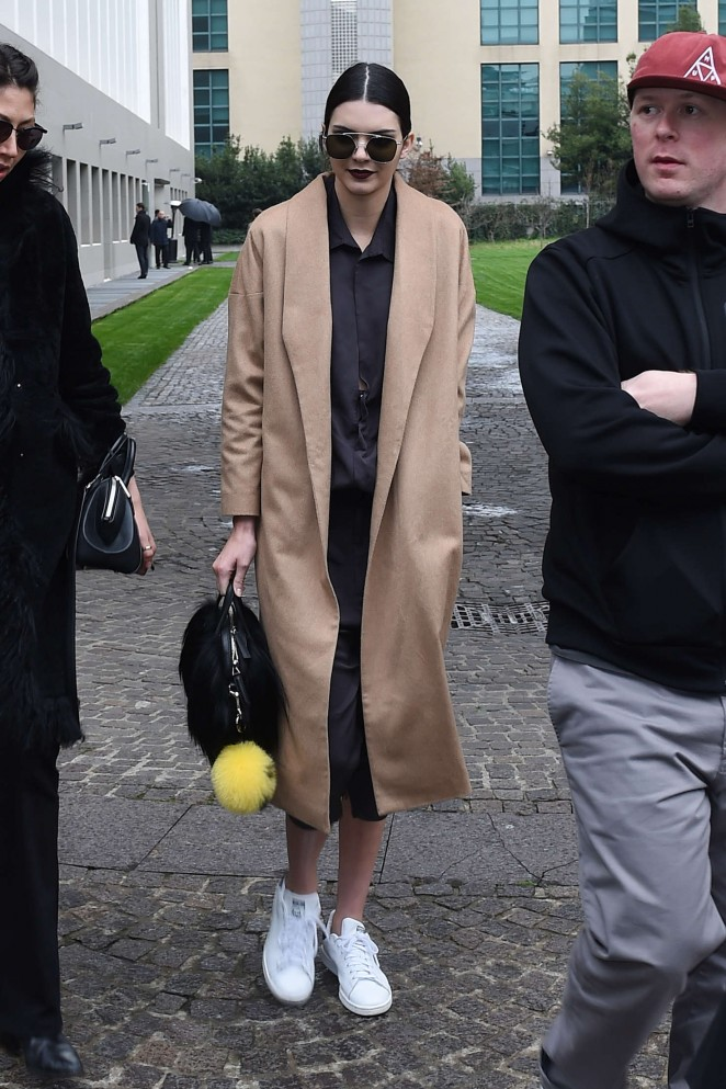 Kendall Jenner is wearing a long camel coat, black jumpsuit, black sunglasses and white Adidas Stan Smith