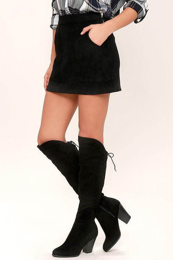 Knee high black suede boots with low wide heels