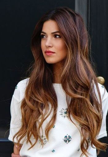 long wavy hair with reddish-brown lowlights and caramel highlights