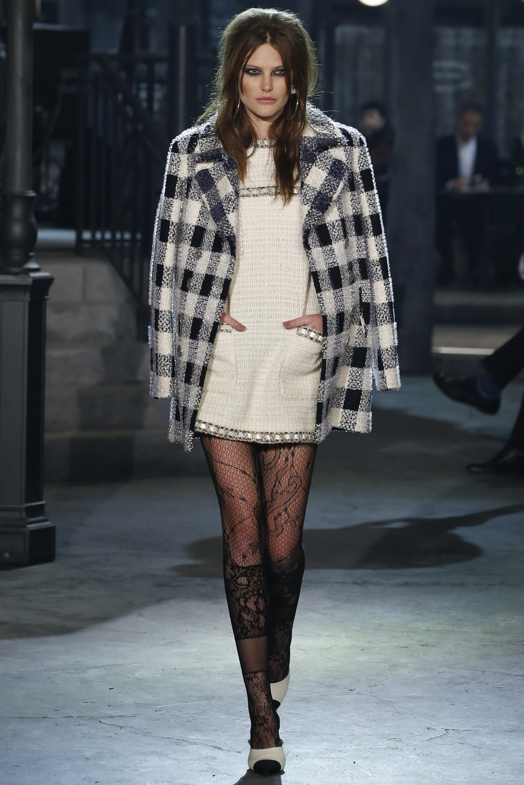 A model is wearing a tweed black and white checked coat with a white mini dress, lace stockings, and black and white heels