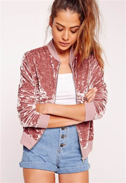A model is wearing a dusty pink velvet bomber jacket, a white t-shirt and high waist denim shorts
