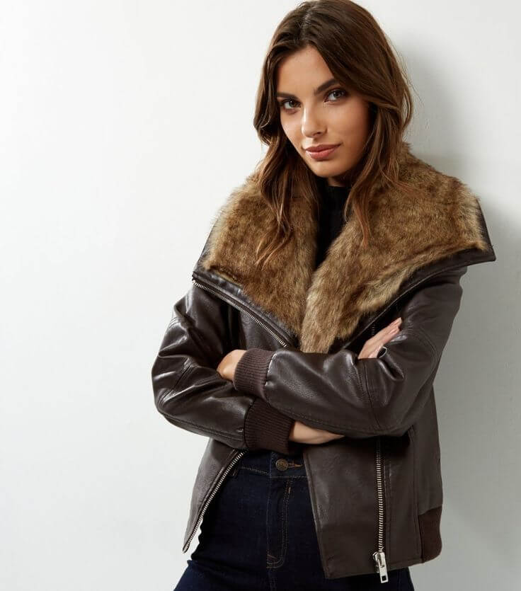 Model in faux fur collar leather bomber jacket