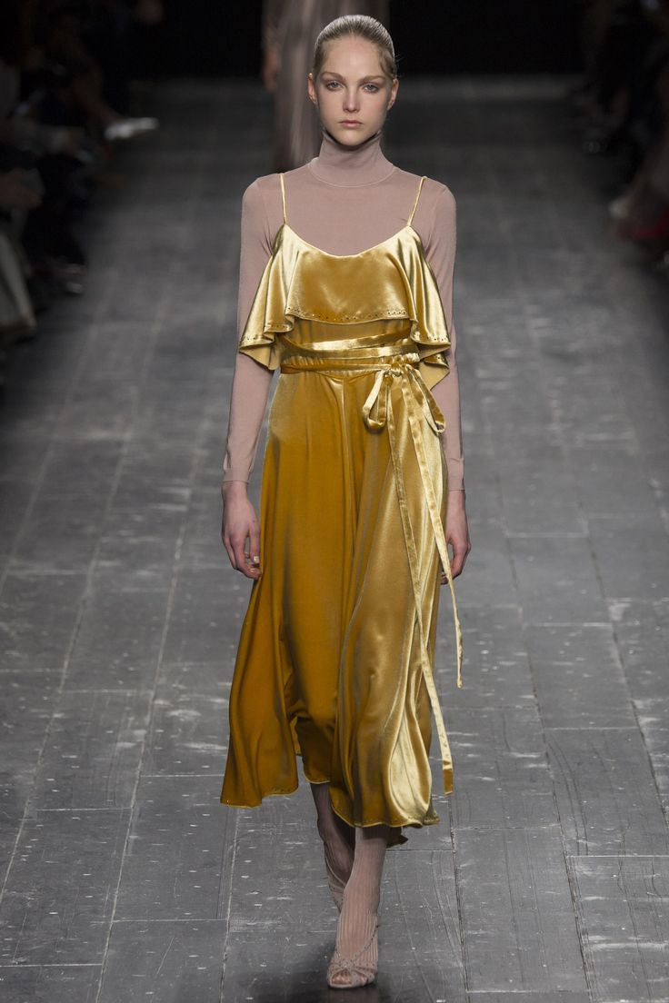 Valentino covers this velvet dress in 'Spicy Mustard' color, with a neutral turtleneck underneath, to lighten up the bright color.