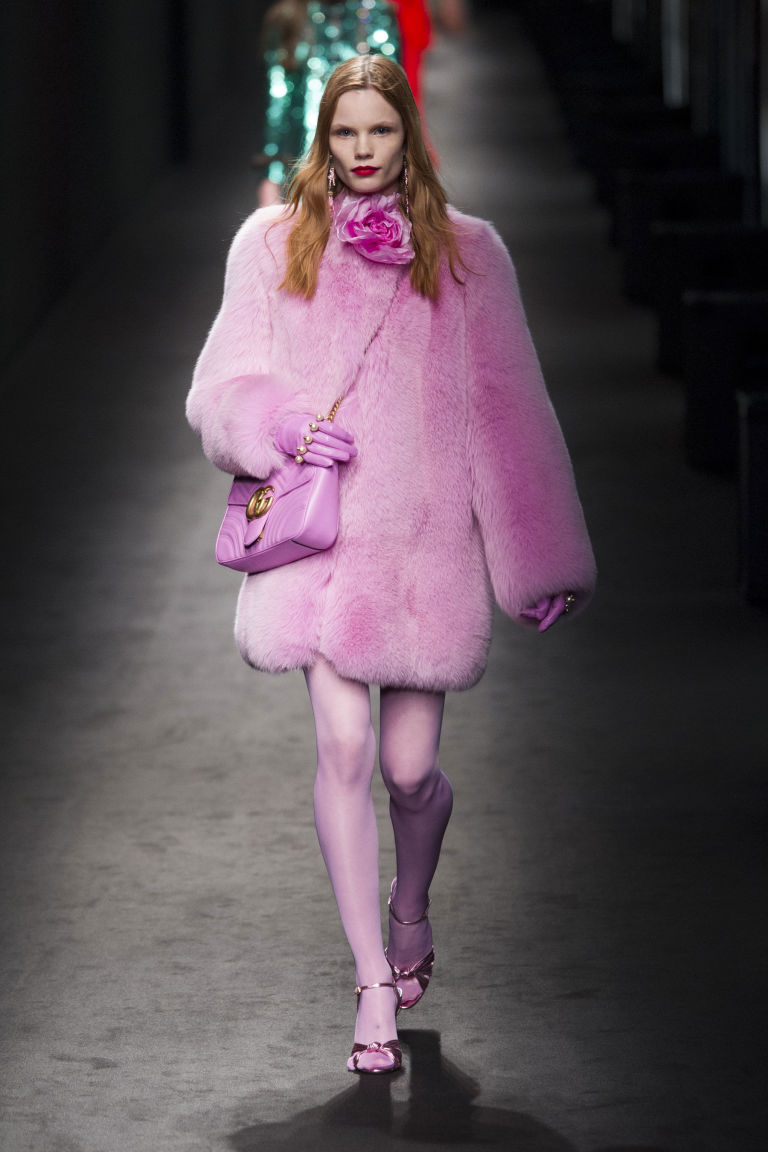 A model from Gucci fashion show is wearing a total pink outfit with oversized fur coat, crossbody bag and stockings, with metallic heels