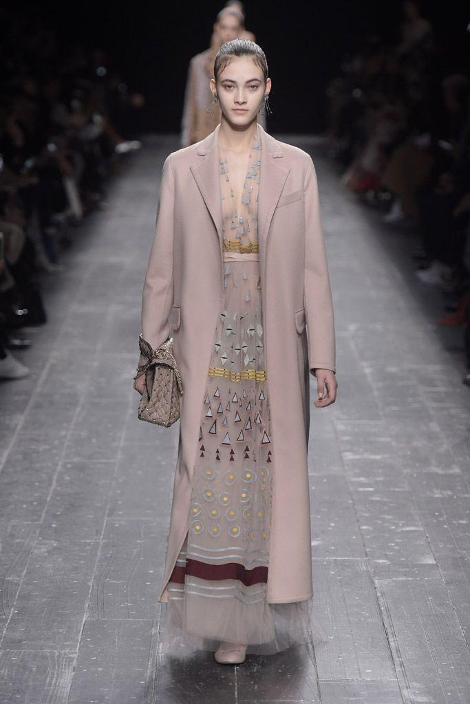 A model on the runway is wearing a light embroidered dress and a long ankle-length pink coat, with a clutch in her hand, all in light vintage pink