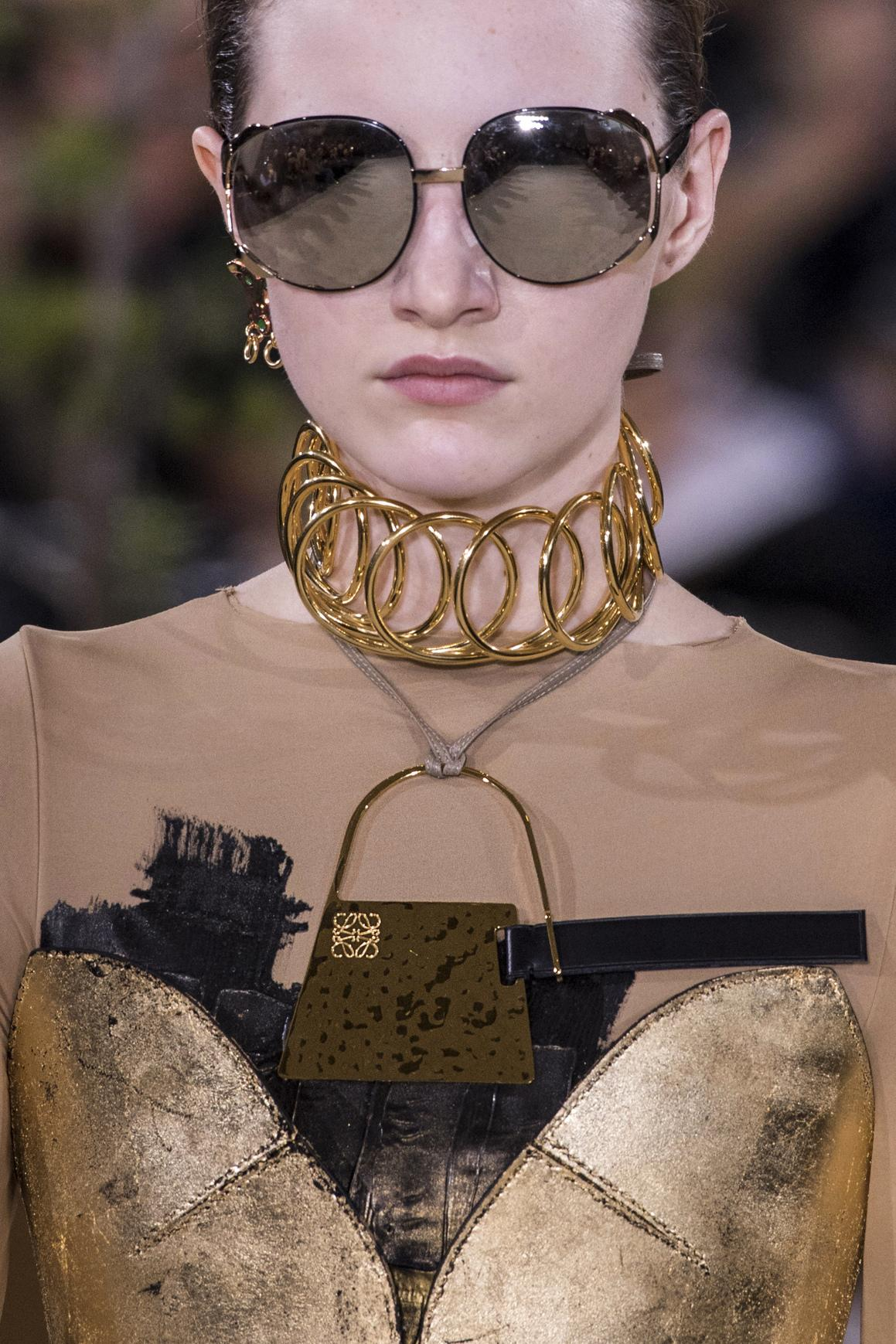 A model is wearing a statement choker made with a golden chain