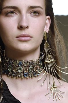 A model is wearing a statement choker with stones and a long metallic earring