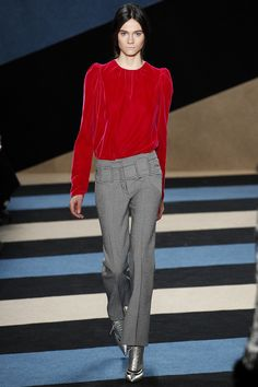 A model is wearing a deep red shirt, gray pants and silver pointy toe shoes