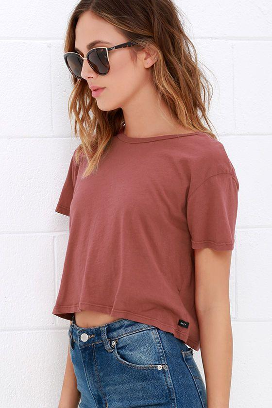 A model is wearing a dusty pink t-shirt with blue jeans and sunglasses