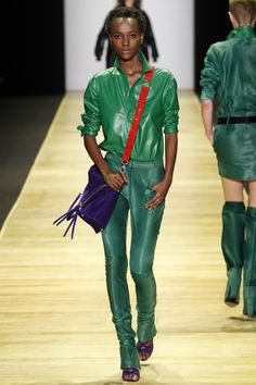 model wearing a green leather outfit of jacket and pants, with purple bag and shoes